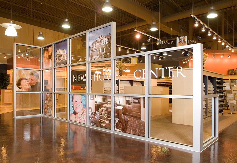A 10 ft x 25 ft glass wall with integrated messaging welcomes visitors to Oakwood's New Home Center. The welcome wall gently directs them to the entry point of the center and uses images of homes and home buyers to reinforce their decision to buy a home from Oakwood.